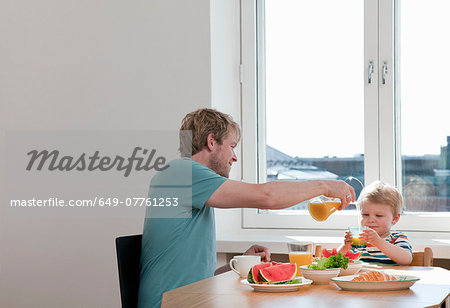 Father and toddler son having breakfast at kitchen table Stock Photo - Premium Royalty-Free, Image code: 649-07761253