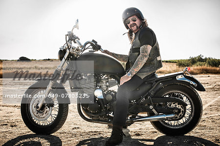 Portrait of mature man on motorcycle on arid plain, Cagliari, Sardinia, Italy Stock Photo - Premium Royalty-Free, Image code: 649-07803235