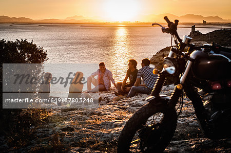 Five motorcycling friends taking a break on coast at sunset, Cagliari, Sardinia, Italy Stock Photo - Premium Royalty-Free, Image code: 649-07803248