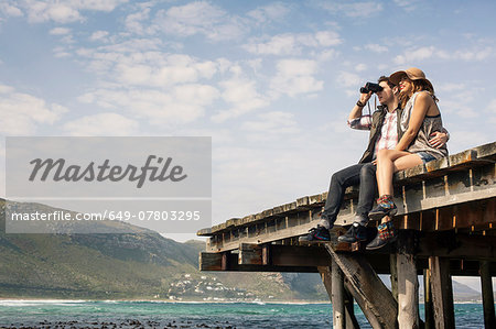 Young couple sitting on edge of old pier looking through binoculars, Cape Town, Western Cape, South Africa Stock Photo - Premium Royalty-Free, Image code: 649-07803295