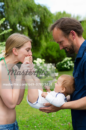 Mother kissing baby daughters feet in garden Stock Photo - Premium Royalty-Free, Image code: 649-07803426