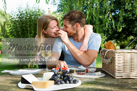 Mid adult man feeding girlfriend from picnic table in garden Stock Photo - Premium Royalty-Free, Image code: 649-07803439