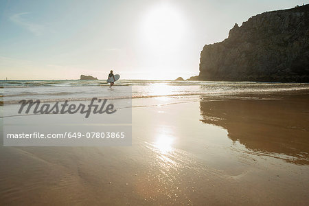 Senior woman walking into sea with surfboard, Camaret-sur-mer, Brittany, France Stock Photo - Premium Royalty-Free, Image code: 649-07803865