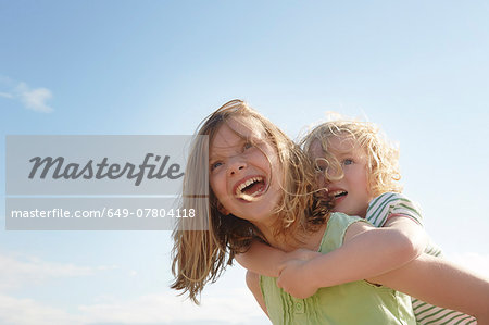 Low angle view of girl giving sister piggy back at coast Stock Photo - Premium Royalty-Free, Image code: 649-07804118