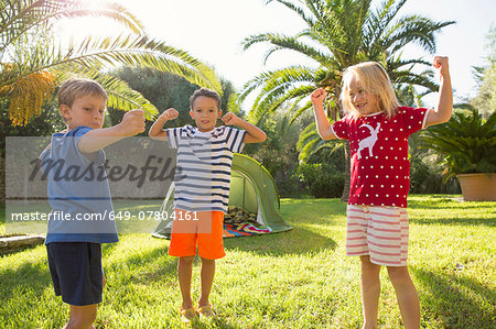 Three children in garden flexing muscles Stock Photo - Premium Royalty-Free, Image code: 649-07804161