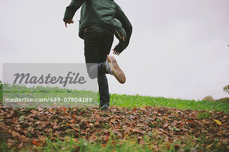 Cropped shot of young man running in field Stock Photo - Premium Royalty-Free, Image code: 649-07804189