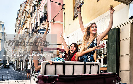 Three young women in open back seat of Italian taxi, Cagliari, Sardinia, Italy Stock Photo - Premium Royalty-Free, Image code: 649-07804267