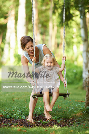 Mid adult mother pushing toddler daughter on garden swing Stock Photo - Premium Royalty-Free, Image code: 649-07804293