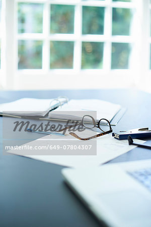 Laptop, eyeglasses and diary on dining room table Stock Photo - Premium Royalty-Free, Image code: 649-07804307