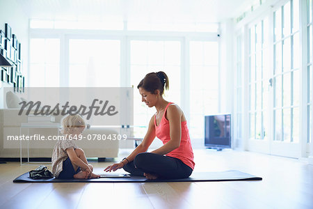 Mid adult mother and toddler daughter practicing yoga in living room Stock Photo - Premium Royalty-Free, Image code: 649-07804309