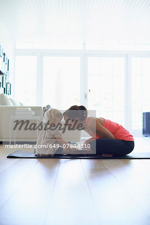 Mid adult mother and toddler daughter practicing lotus position in living room Stock Photo - Premium Royalty-Free, Image code: 649-07804310