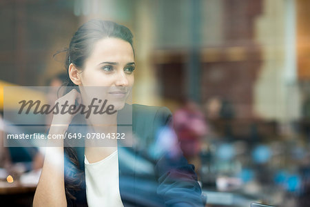 Young businesswoman looking out of cafe window, London, UK Stock Photo - Premium Royalty-Free, Image code: 649-07804322