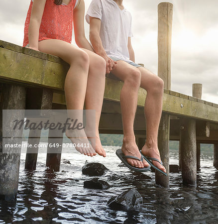 Young couple holding hands together and sitting on edge of jetty over lake Stock Photo - Premium Royalty-Free, Image code: 649-07804411