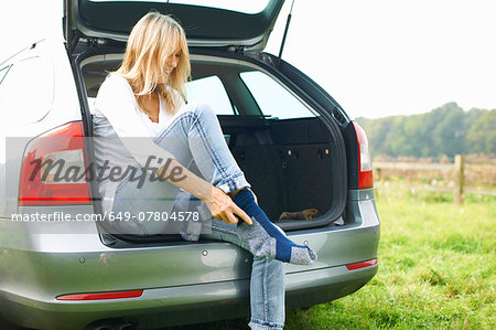 Woman sitting at rear of car putting on socks Stock Photo - Premium Royalty-Free, Image code: 649-07804578