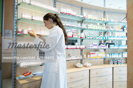 Pharmacist in pharmacy looking at medicine box Stock Photo - Premium Royalty-Free, Image code: 649-07804632