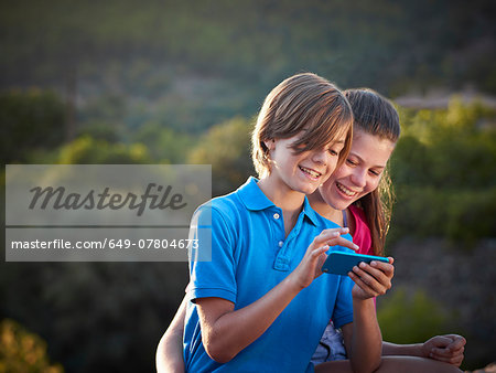 Brother and teenage sister using touchscreen on smartphone, Majorca, Spain Stock Photo - Premium Royalty-Free, Image code: 649-07804673