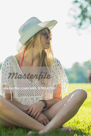 Young woman wearing white sunhat sitting cross legged Stock Photo - Premium Royalty-Free, Image code: 649-07804704
