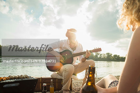 Young man sitting by lake playing guitar Stock Photo - Premium Royalty-Free, Image code: 649-07804731