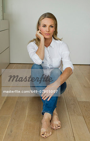 Mature woman sitting on wooden floor, portrait Stock Photo - Premium Royalty-Free, Image code: 649-07805007