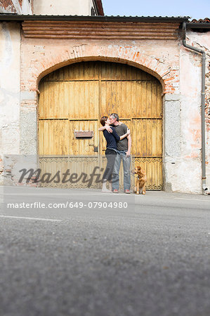 Couple kissing in front of building entrance on street, Suno, Novara, Italy Stock Photo - Premium Royalty-Free, Image code: 649-07904980