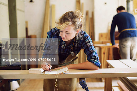 Young craftswoman making notes in pipe organ workshop Stock Photo - Premium Royalty-Free, Image code: 649-07905021
