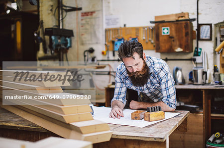 Mid adult craftsman looking down at blueprint in organ workshop Stock Photo - Premium Royalty-Free, Image code: 649-07905028