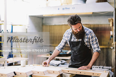 Cropped shot of mid adult craftsman measuring wood in organ workshop Stock Photo - Premium Royalty-Free, Image code: 649-07905037