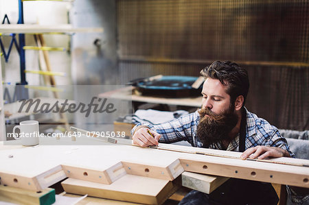 Cropped shot of mid adult craftsman measuring wood component in organ workshop Stock Photo - Premium Royalty-Free, Image code: 649-07905038