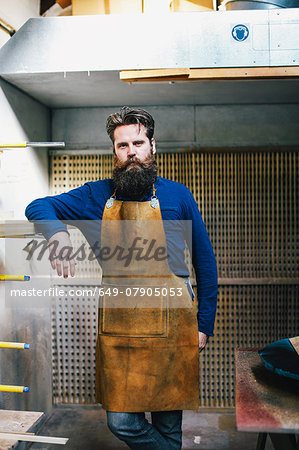 Portrait of mid adult craftsman leaning on shelf in organ workshop Stock Photo - Premium Royalty-Free, Image code: 649-07905053