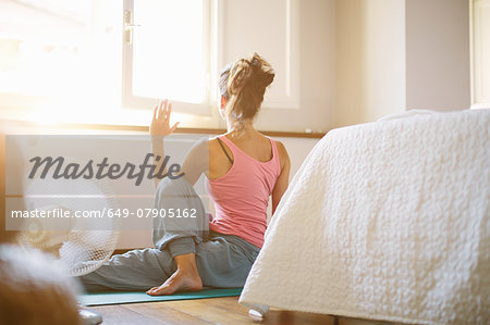 Mid adult woman practicing yoga on bedroom floor Stock Photo - Premium Royalty-Free, Image code: 649-07905162