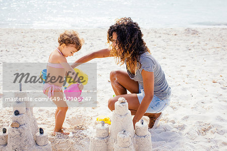 Mother and toddler daughter building sandcastle on beach, Tuscany, Italy Stock Photo - Premium Royalty-Free, Image code: 649-07905247