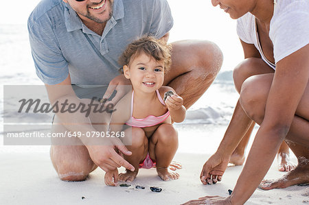 Couple with two girls searching for seashells on beach, Tuscany, Italy Stock Photo - Premium Royalty-Free, Image code: 649-07905268
