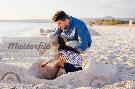 Girl and father with sophisticated car sandcastle on beach, Tuscany, Italy Stock Photo - Premium Royalty-Free, Image code: 649-07905278