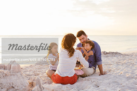Couple with two girls picnicing with cakes on beach, Tuscany, Italy Stock Photo - Premium Royalty-Free, Image code: 649-07905281