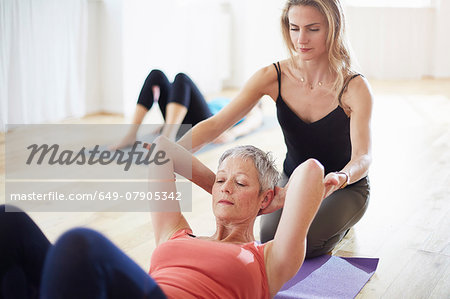 Pilates teacher holding student arms in class Stock Photo - Premium Royalty-Free, Image code: 649-07905342