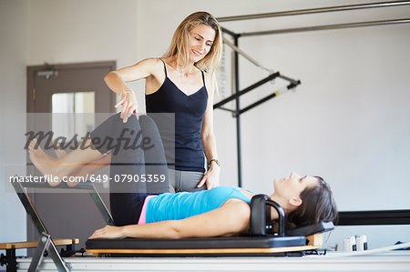 Female student lying on reformer in pilates gym Stock Photo - Premium Royalty-Free, Image code: 649-07905359
