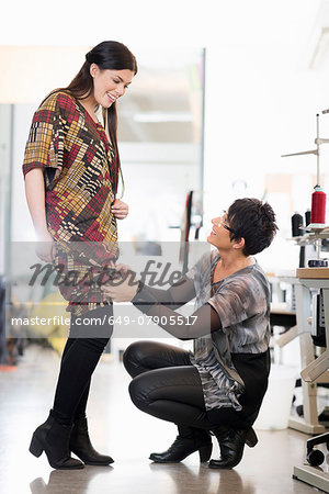 Mature seamstress adjusting length of customers dress in workshop Stock Photo - Premium Royalty-Free, Image code: 649-07905517