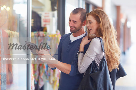 Couple window shopping, holding digital tablet Stock Photo - Premium Royalty-Free, Image code: 649-07905644