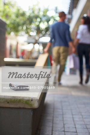 Mid adult couple walking with shopping bags, wallet left on seat behind them Stock Photo - Premium Royalty-Free, Image code: 649-07905649