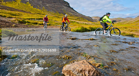 Three mountain bikers cycling through hot river,  Reykjadalur valley, South West Iceland Stock Photo - Premium Royalty-Free, Image code: 649-07905698
