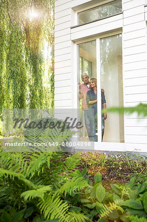 Husband and wife looking out of window into garden Stock Photo - Premium Royalty-Free, Image code: 649-08004098