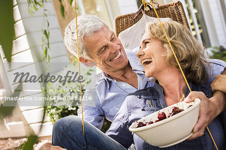 Husband and wife relaxing with bowl of cherries on hammock Stock Photo - Premium Royalty-Free, Image code: 649-08004114