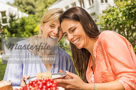 Two female friends in garden, laughing, holding plate with dessert Stock Photo - Premium Royalty-Free, Image code: 649-08004191