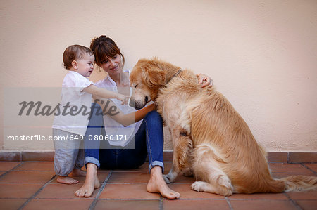 Mid adult woman with baby daughter petting dog in kitchen Stock Photo - Premium Royalty-Free, Image code: 649-08060171