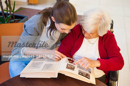 Mid adult woman and her grandmother pointing and looking at photograph album Stock Photo - Premium Royalty-Free, Image code: 649-08060313