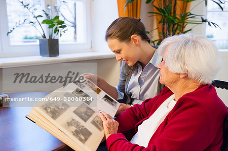 Mid adult woman and her grandmother looking at photograph album Stock Photo - Premium Royalty-Free, Image code: 649-08060314