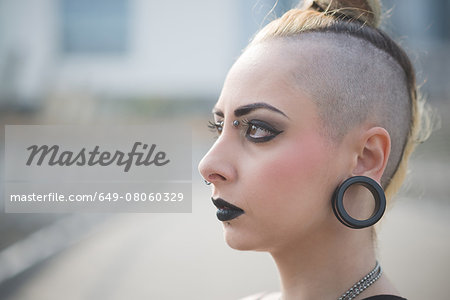 Portrait of young female punk with earlobe piercing and shaved head Stock Photo - Premium Royalty-Free, Image code: 649-08060329