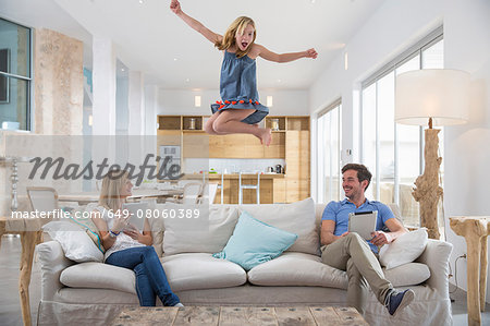 Girl jumping mid air from living room sofa whilst parents use digital tablet Stock Photo - Premium Royalty-Free, Image code: 649-08060389