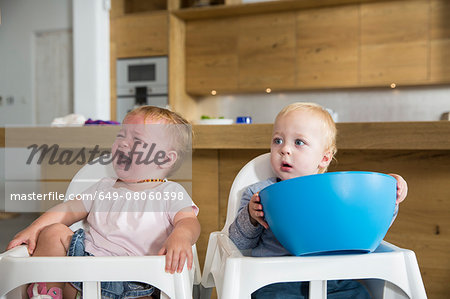 Male and female twin toddlers in high chairs Stock Photo - Premium Royalty-Free, Image code: 649-08060398