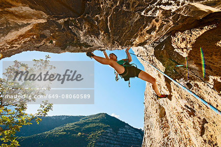 Female climber, climbing out of a cave with an old quarry in the background, Finale Ligure, Savona, Italy Stock Photo - Premium Royalty-Free, Image code: 649-08060589